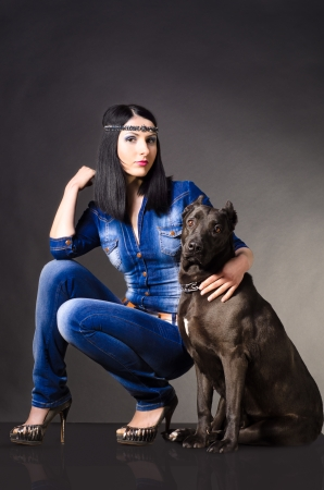 Beautiful young woman in jeans clothes sitting next to the dog