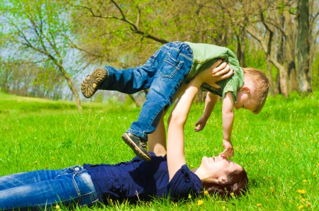 Young mother with son having fun outdoors