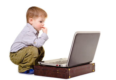 Little boy thoughtfully sits at a notebook Stock Photo