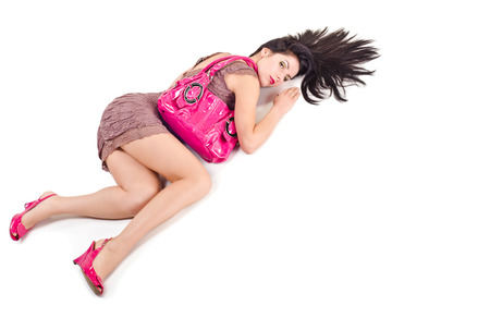 Woman lying with disheveled hair and holds on shoulder bag photo