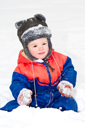 Portrait of little beautiful boy sitting on the snow