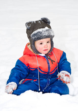 ��beautiful boy�: Portrait of beautiful boy sitting on the snow Stock Photo