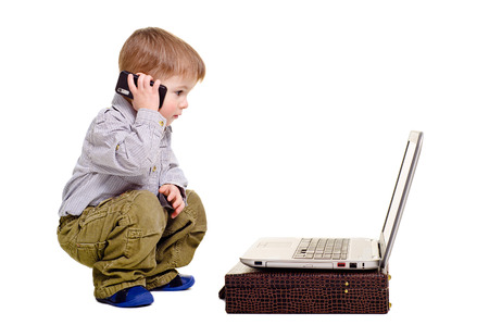 Beautiful boy speaks on the phone looking at laptop Stock Photo