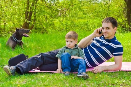 Man  with son and dog outdoors talking on the phone Stock Photo
