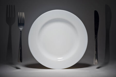 Plate and fork with knife hanging in the air