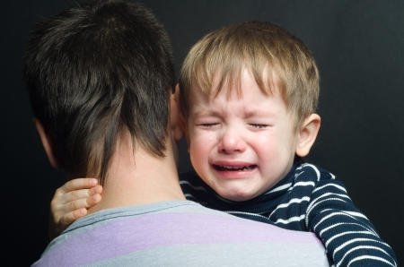 彼の父の腕の中で泣いている子