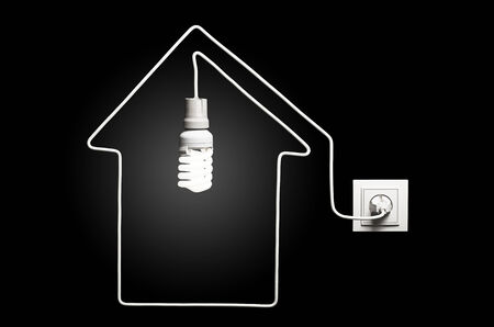 Light in the house  Glowing lightbulb in a house on a black background photo