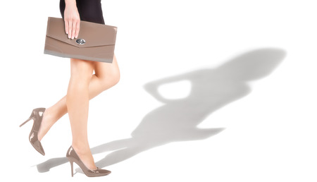 Slender woman feet in beige shoes and shade