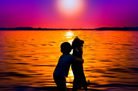 Silhouette of boy and dog hugging at sunset photo