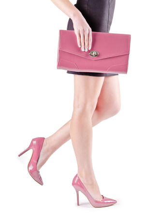 Slender beautiful female feet in pink shoes and mini bag