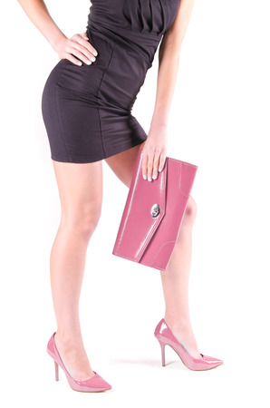 Slender beautiful female legs in pink shoes and mini bag Stock Photo