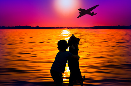 Silhouette of boy and dog at sunset watching aircraft photo