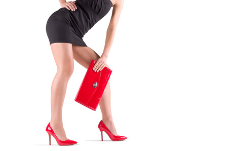 mini purse: Slender beautiful female legs in red shoes and mini bag