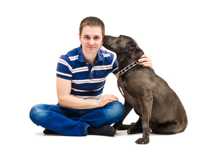 Young man and his licking dog photo