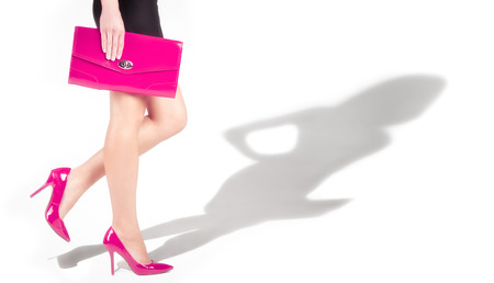 Beautiful slender female legs in pink shoes, the shadow of the model photo