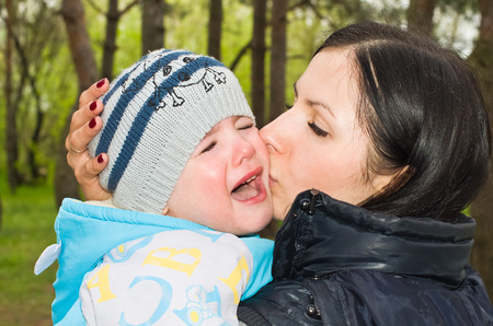 whining: Portrait of a crying child in mother s arms Stock Photo