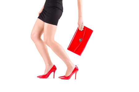 Beautiful slender female legs in red shoes and bag in hand photo