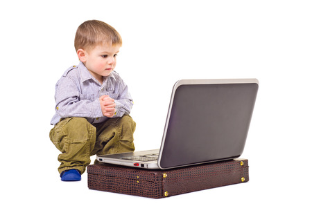 3 4 length: Cute little boy sitting near a laptop