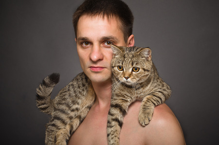 Portrait of a young man with a cat on his shoulders