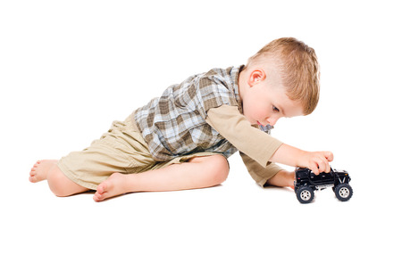 かわいい男の子が白い背景で隔離のおもちゃの車を再生