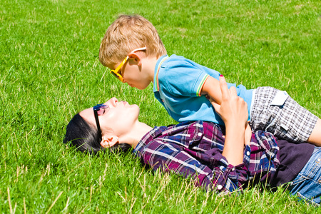 Mother and son kissing lying on the grass photo