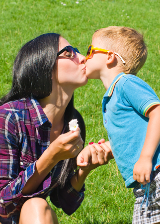 Portrait of mother and son kissing outdoors photo