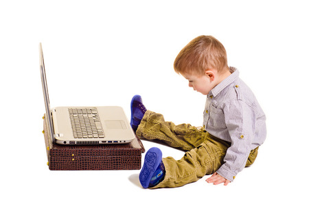 3 4 length: Cute little boy sitting before a laptop