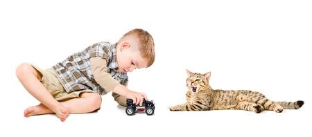 ��beautiful boy�: Beautiful boy playing toy car near the yawning cat