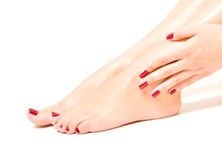 Pés fêmeas bonitos e mãos com prego vermelho polonês