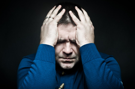 poorly: Portrait of a frustrated young man holding on to head Stock Photo