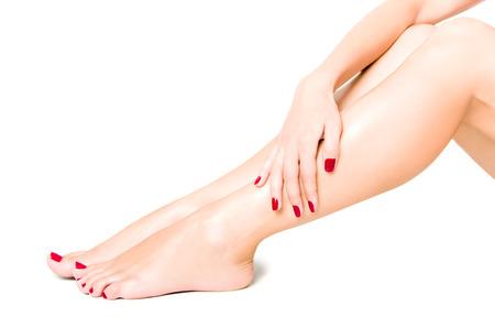 pedicura: Hermosas piernas femeninas bien cuidadas con pedicure rojo aisladas sobre fondo blanco Foto de archivo