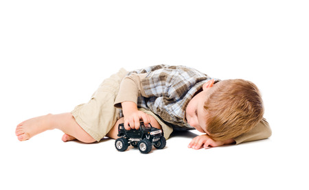 Child plays a toy car isolated on white background photo