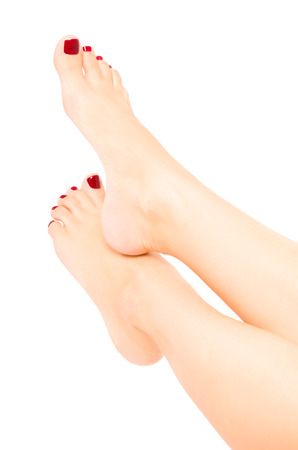 Beautiful  female feet with red pedicure isolated on white background