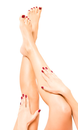 Beautiful female legs and hands with red pedicure
