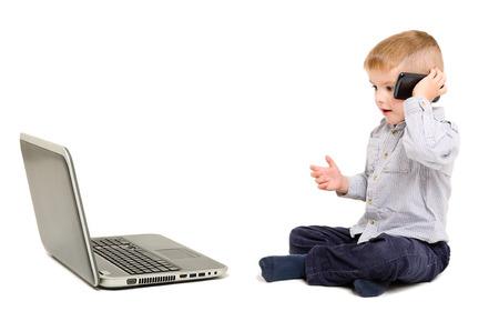 ��beautiful boy�: Beautiful boy talking on the phone sitting next to a laptop