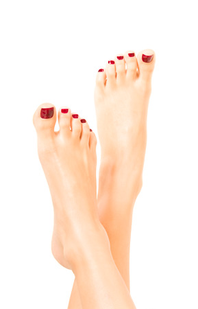 red nail colour: Beautiful well-groomed female feet with red pedicure Stock Photo