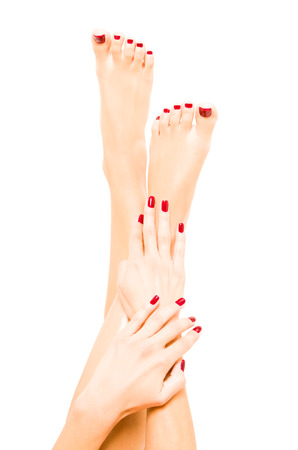 Well-groomed female feet and hands with red polish Foto de archivo