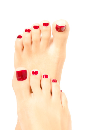Beautiful female foot with red pedicure isolated on white background Фото со стока