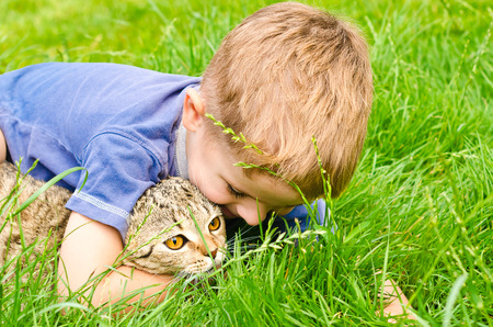 Cheerful boy hugging cat lying in the grass photo