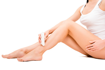 laser treatment: Beautiful young woman removes hair from the legs using the epilator