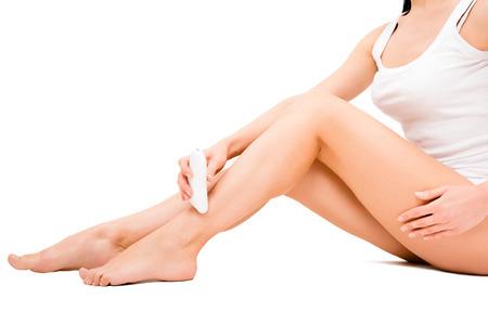 depilacion: Mujer joven hermosa que elimina el vello de las piernas usando la depiladora