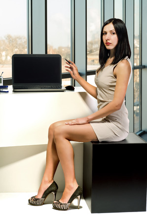 Young attractive woman in the workplace in the office indicates on the laptop screen photo