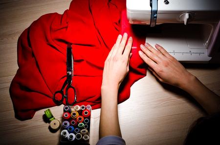 m�quina de coser: Manos femeninas en el trabajo en la m�quina de coser, vista de cerca, la parte superior. Foto de archivo