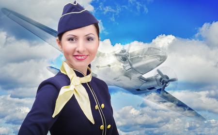空を飛んでいる飛行機の背景に若い美しいスチュワーデスの肖像画 写真素材