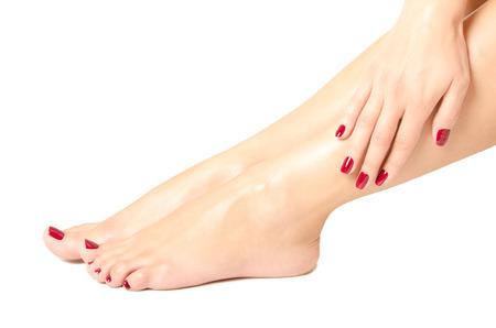 Mooie vrouwelijke voeten en handen met rode manicure op een witte achtergrond Stockfoto