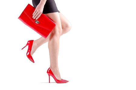 mini purse: Beautiful walking female legs in red shoes isolated on white background