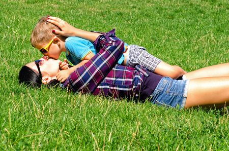 mom kiss son: Young mother and son kissing lying on the lawn Stock Photo