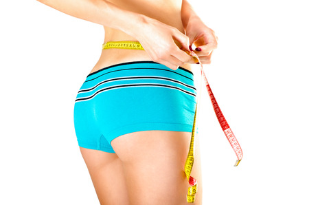 centimetre: Slim young woman measuring waist a centimetre ribbon isolated on white background