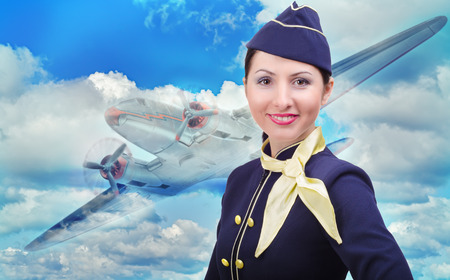 Portrait of beautiful smiling stewardess on a background of an airplane flying in the sky photo