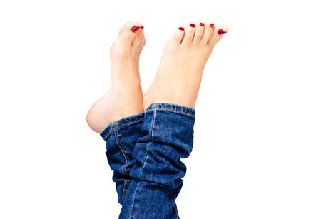 Beautiful female groomed feet with red nail polish in jeans closeup isolated on white background